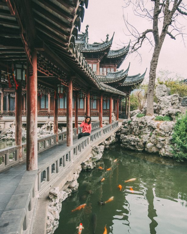 Yu garden architecture chinese women with pink sweater next to the pond