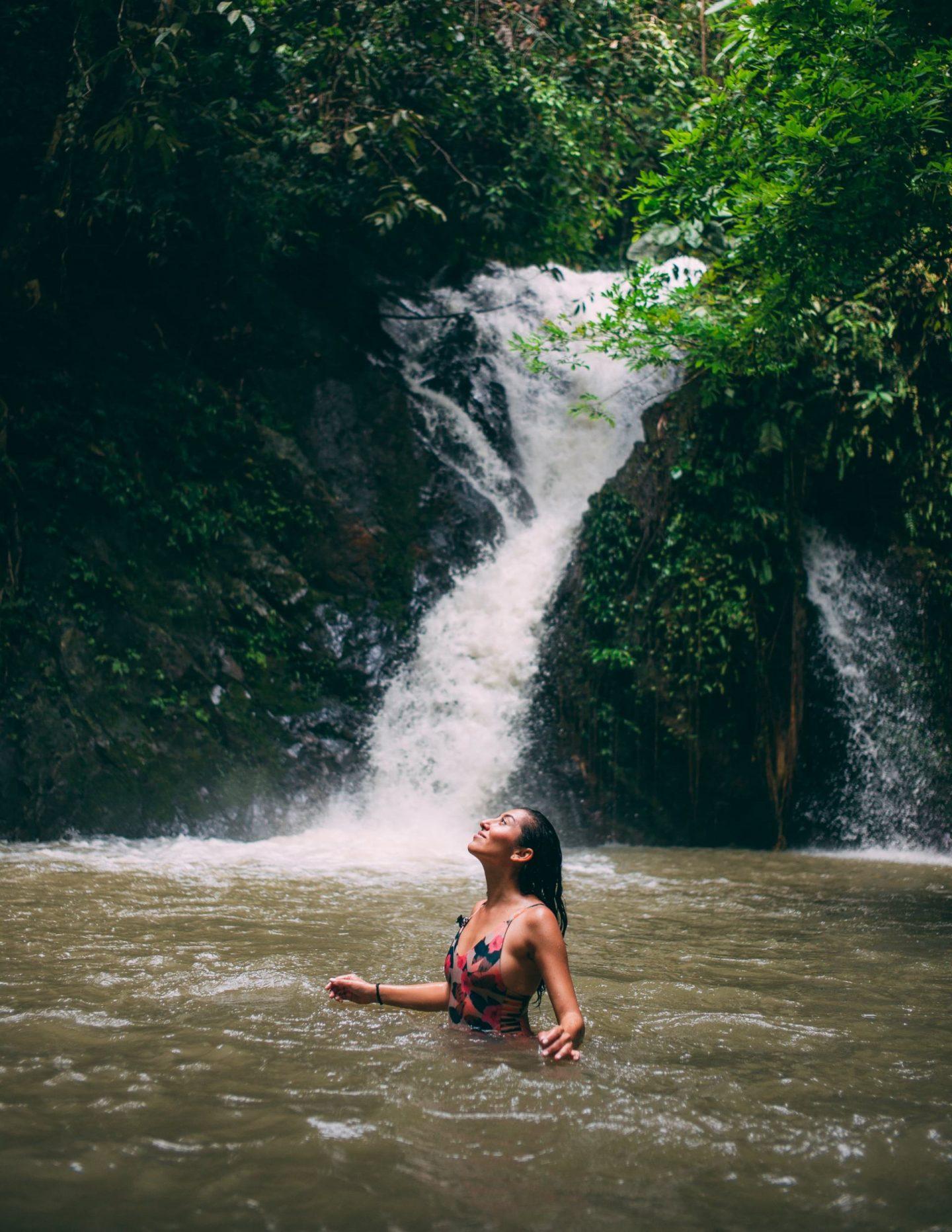 women swimming in waterfall
