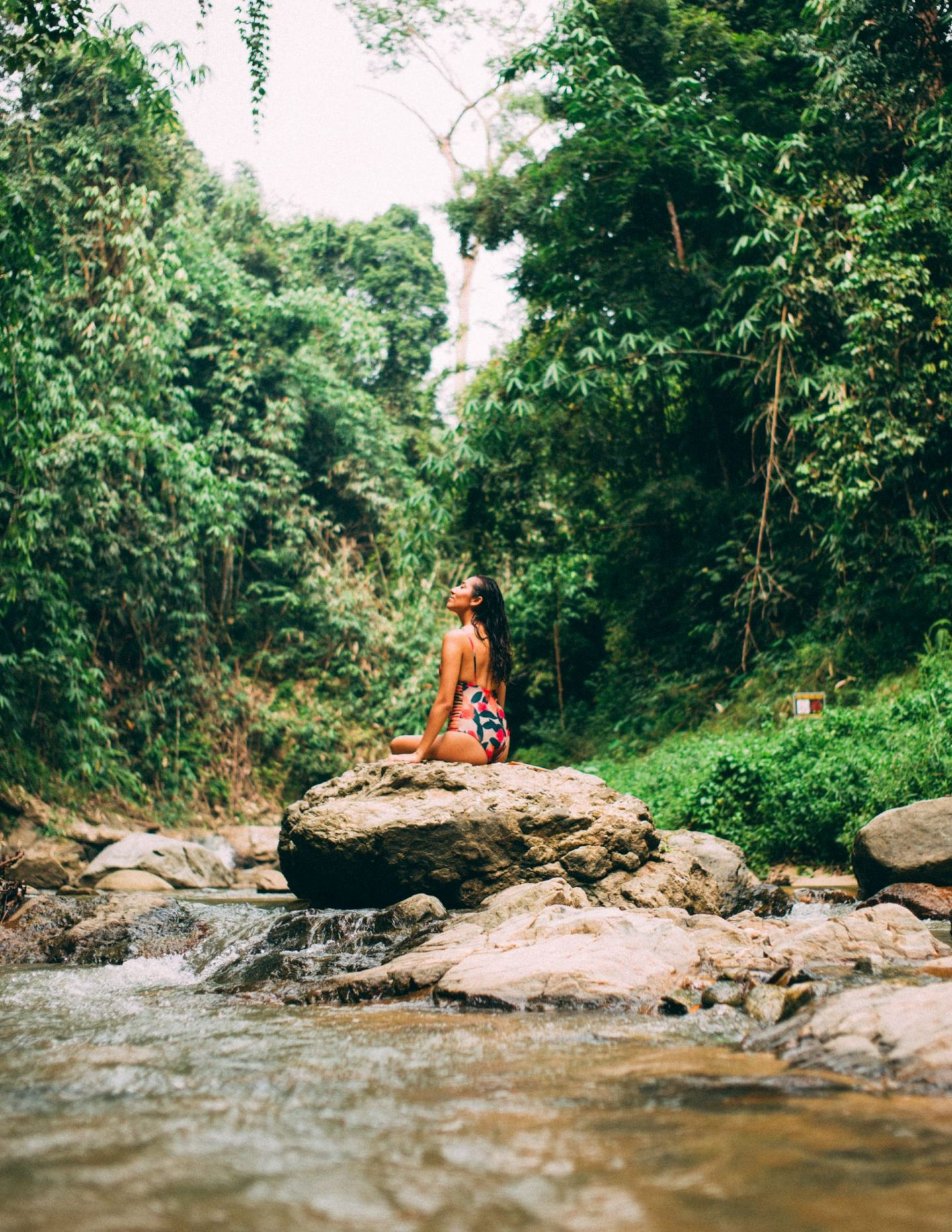 women sitting in a rock in the middle of the jungle