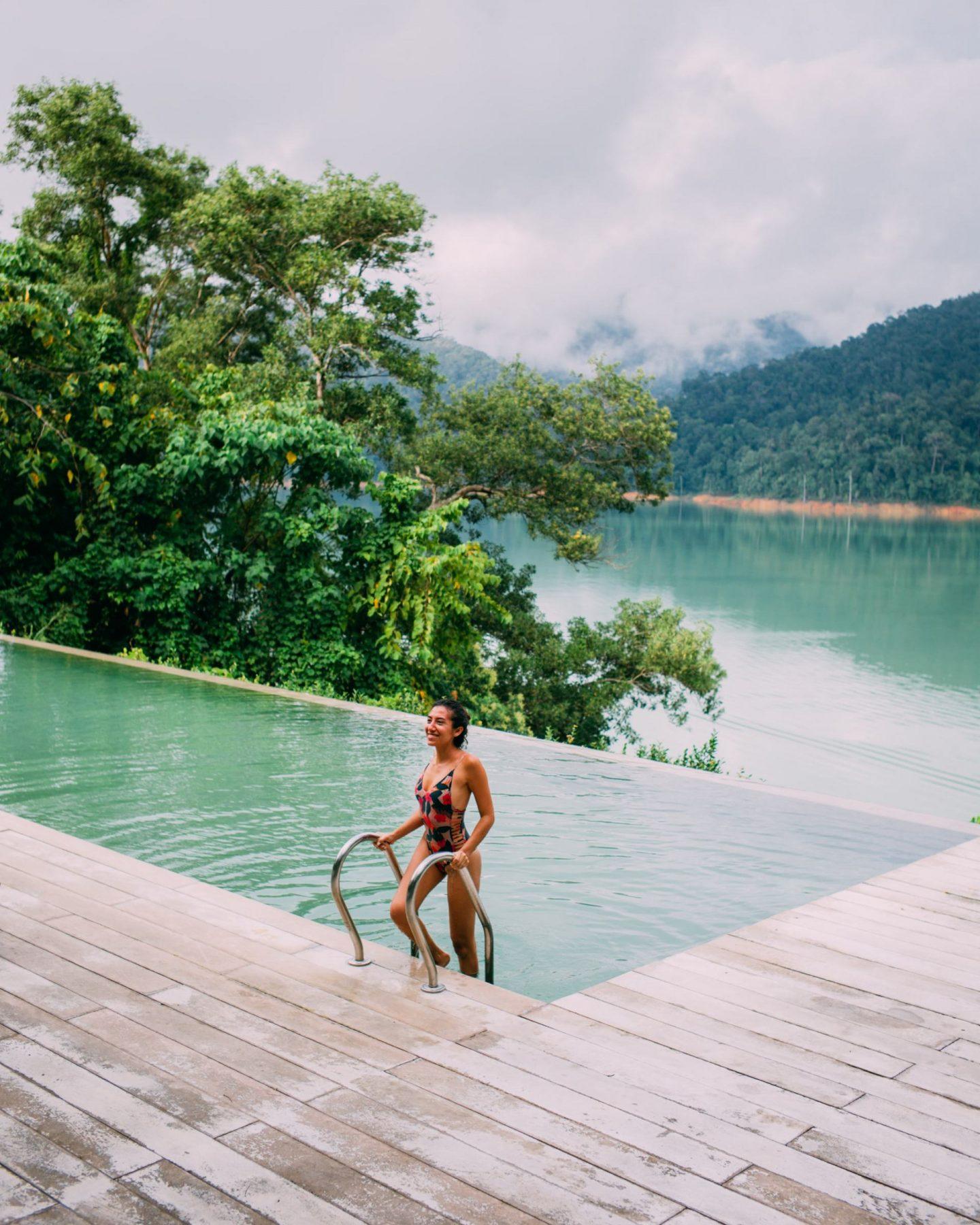 women in swimming pool next to a lake
