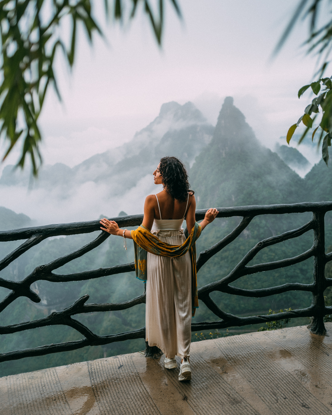 foggy mountains in the horizon with a women watching the view